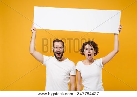 Irritated Young Couple Friends Bearded Guy Girl In White T-shirts Isolated On Yellow Orange Backgrou