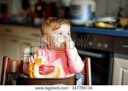 Cute Little Baby Girl Eating Bread. Adorable Child Eating For The First Time Piece Of Pretzel Or Cro