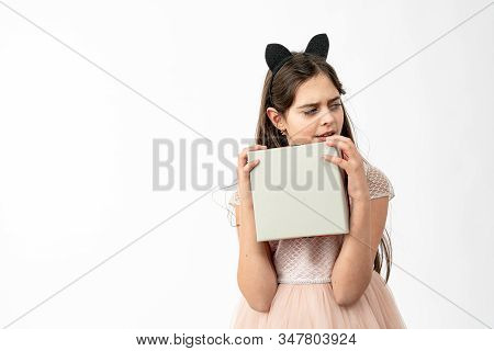 Thrilled, Excited Brunette Girl In Beige Dress Holds White Box In Hands And Looking At Right Side Is