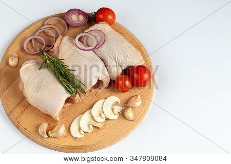 On A Wooden Board, Skinless Chicken Thighs, Next To Mushrooms, With Tomatoes, Red Onions And Thyme.