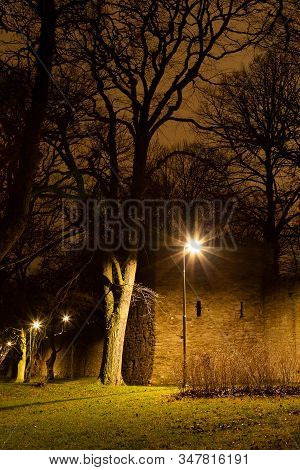 Street Lights And Trees By Town Wall In Visby, Sweden.