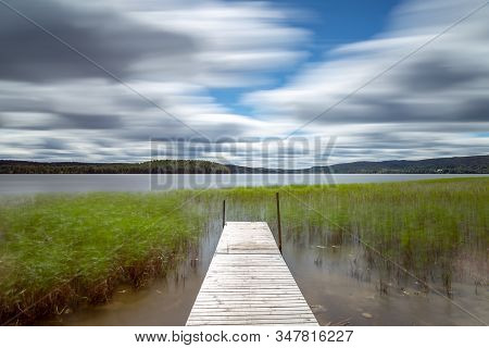 Pier In The Tavelsjo Lake, Sweden With A Cloudy Sky.