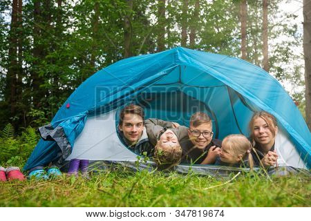 Five children of different age lying together in tent camping in a summer forest enjoying summer holidays outdoor