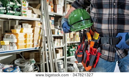 Electrician In The Electrical Component Store Wears Protective Gloves And Holds Helmet And Goggles I