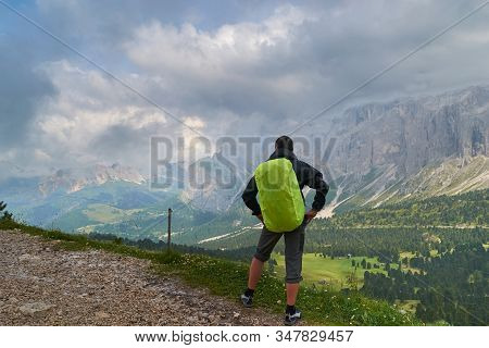 Man With Backpack And Green Rain Cover Looking At The Stormy Clouds Towards A Valley Bellow Sella Mo