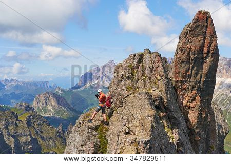 Adventure Photographer Looking Around From A Small Ridge Up On Via Ferrata Delle Trincee, In Dolomit