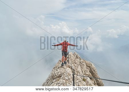 Climber Finding His Balance On Top Of A Mountain Ridge, Surrounded By Clouds, High On Via Ferrata Et