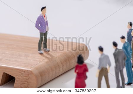 Team Leader Addressing A Group Of Miniature Figures Of Business Colleagues Standing On An Elevated W