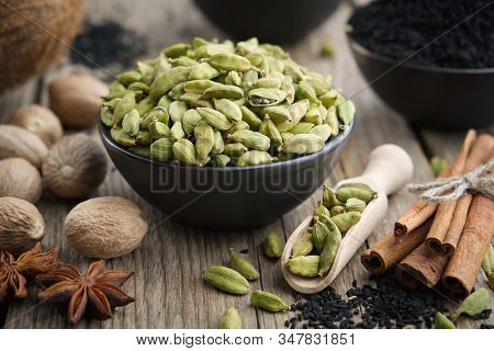 Green Cardamom Pods In Black Ceramic Bowl. Aromatic Spices: Anise, Gloves, Black Cumin Seeds, Nutmeg
