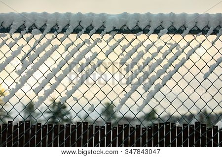 A Selective Focus View Of A Chain Link Diamond Mesh Fence Creating A Barrier During Winter, Covered