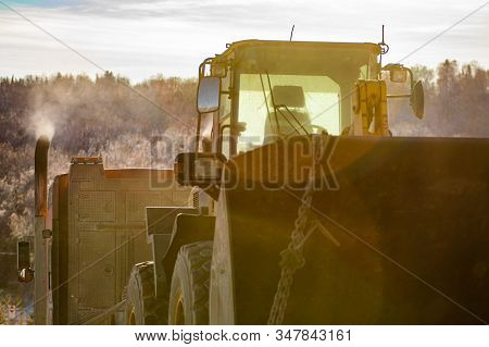 A Close Up Shot On The Rear Of A Tractor And Bucket Chained To A Flatbed Wagon During Winter With Le