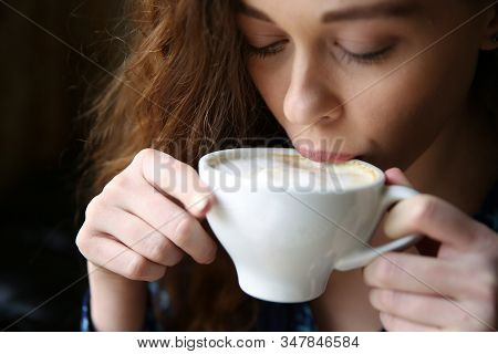 Young Woman Is Drinking Coffee Latte  With Foam Closeup. European Lady Holds Cup With Cappuccino Clo