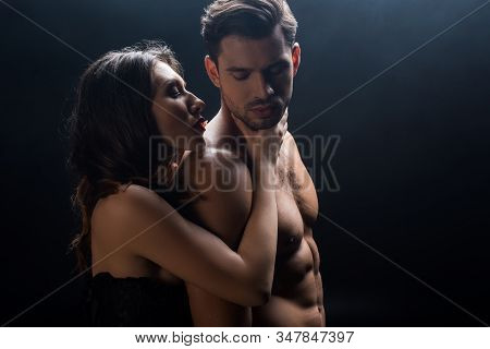 Side View Of Attractive Woman Holding By Neck Handsome Shirtless Man Isolated On Black