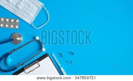 Frame Of Medical Equipment On Blue Background. Flat Lay Medical Clipboard, Stethoscope, Pills, Syrin