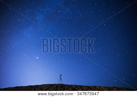 Night Photography. Silhouette Of Camera On Tripod On Background Of Starry Sky. Long Exposure. Many S