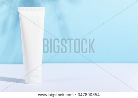 Feminine Hygienic Product Tube On Sunny Blue Background With Leaf Shadow. Shampoo, Hand Cream, Tooth