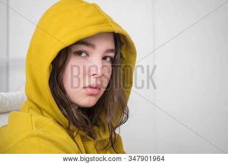Unhappy teenager girl in a hoodie in her room, close-up face
