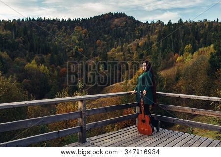 Long-haired Girl Holds Guitar, Standing Near Parapet In Mountains In Autumn.