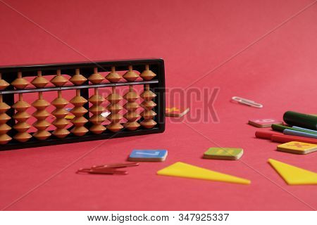 Mental Arithmetic And Math Concept: Colorful Pens And Pencils, Numbers, Abacus Scores On Red Backgro