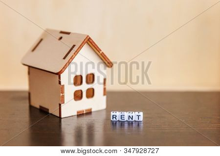 Miniature Toy Model House With Inscription Rent Letters Word On Wooden Backdrop. Eco Village Abstrac