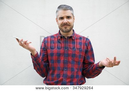 Bearded Young Man Holding Smartphone And Shrugging Shoulders. Stylish Guy Having Confused Look Facin
