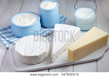 Dairy products: tree types of cheese - Brie, Camembert, and Parmesan, a cup of milk and two pots of yogurt on a rustic table