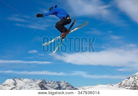 Freestyle Ski Jumper With Crossed Skis In Air With Blue Sky Background In The Snowy Mountains. Livig