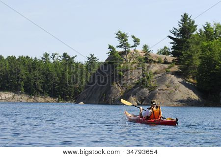 A Man Kayaks Past Rock Formations A Quiet Lake In Northern Ontario, Canada.