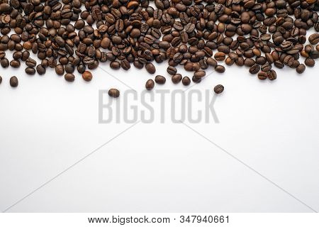 Coffee. Brown Coffee Beans On White Paper Background. Coffee Beans At The Top Of The Picture. Coffee