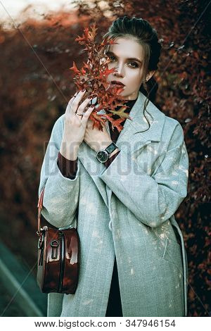 Young Fashionable Beautiful Girl In A Long Gray Coat, Black Jeans And With A Dark Red Bag. Portrait