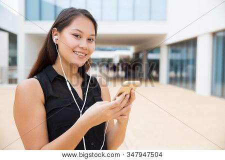 Happy Young Woman In Earphones Using Smartphone. Cheerful Young Female College Student Wearing Earph