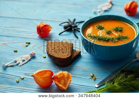 Autumn Cream Soup Garnished With Dill In The Form Of Funny Faces Halloween Pumpkins. Healthy Pumpkin