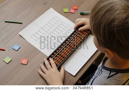 Little Boy Doing Simple Math Exercises With Abacus Scores. Mental Arithmeric. View From Shoulder