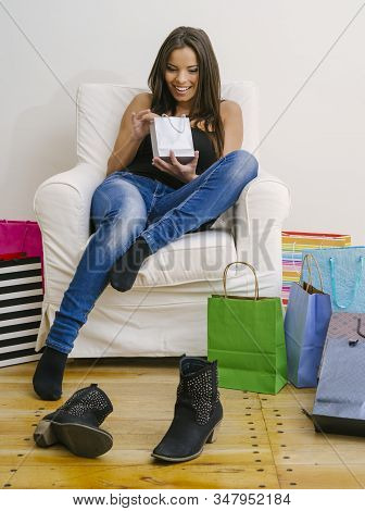 Beautiful Smiling Young Woman Back Home From Shopping, Sitting And Looking In Her Bags.