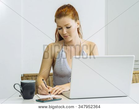 Beautiful Young Woman With Red Hair Sitting With A Laptop And Writing On A Notepad.