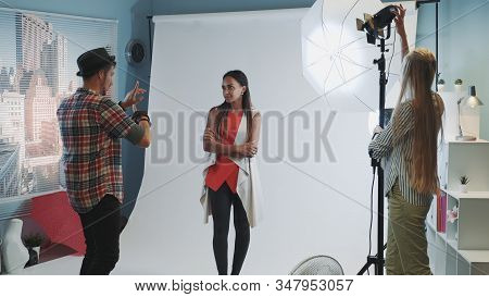 Professional Photographer Explaining Organisational Moments Of The Photo Shoot In Modern Studio. The