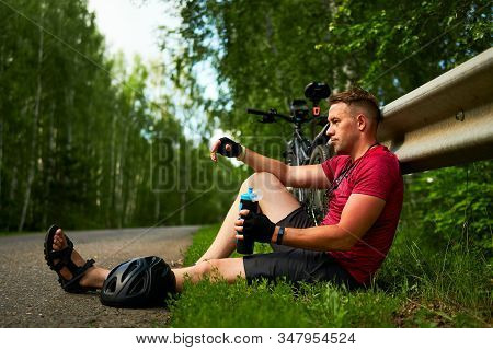 A Tired Cyclist Is Sitting On The Side Of The Road. A Man With A Bicycle Is Resting.