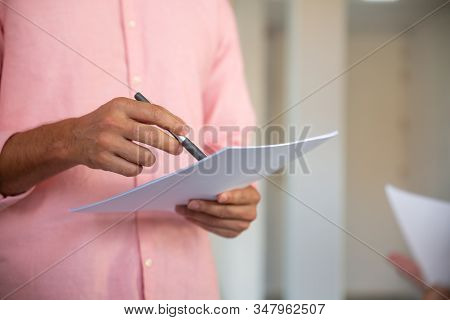 Closeup Shot Of Male Hands Holding Paper Sheet And Pen. Cropped Shot Of Young Man Pointing With Pen