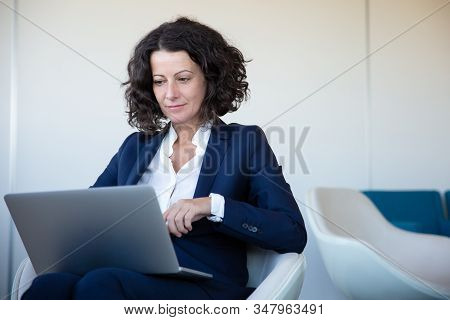 Focused Businesswoman Using Laptop In Office. Concentrated Middle Aged Business Woman Sitting And Wo