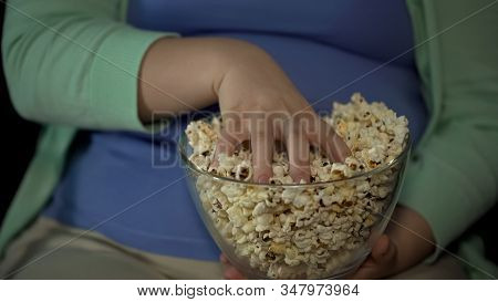 Chubby Woman Taking Handful Of Fatty Popcorn, Sedentary Lifestyle, Overweight