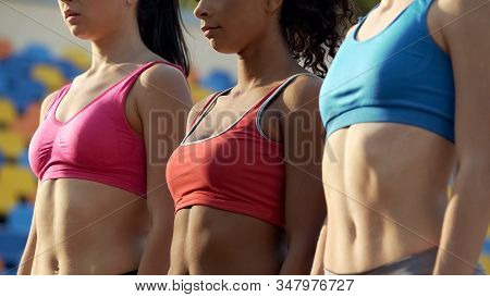 Multiracial Team Of Slim Female Athletes Standing Together Before Competition