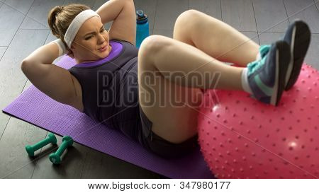 Overweight Lady Doing Press-up Exercises With Gymnastic Ball At Home, Workout