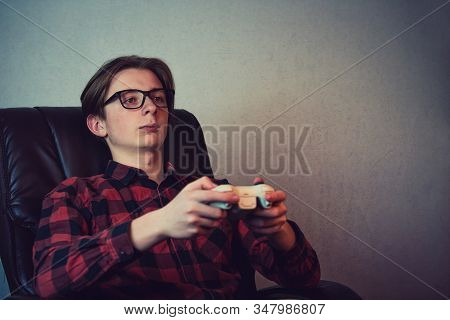 Serious Adolescent Boy Playing Video Games Late Night Seated Relaxed In His Armchair Over Grey Wall