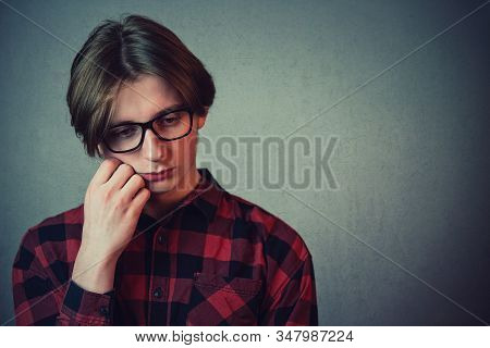 Closeup Portrait Of Sad And Thoughtful Teen Guy, Hand Under Cheek, Looking Down As Feel Guilty And A