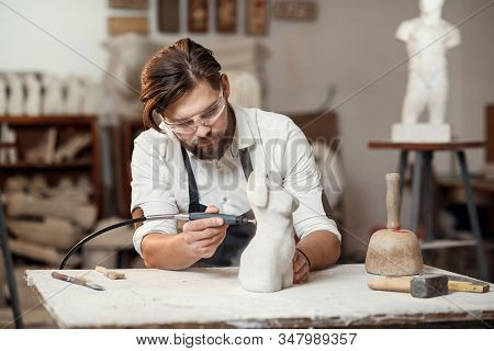 Male Sculptor Repairing Gypsum Sculpture Of Womans Head At The Working Place In The Creative Artisti
