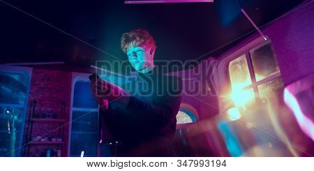 Delighted. Cinematic Portrait Of Stylish Redhair Man In Neon Lighted Interior. Toned Like Cinema Eff