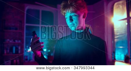 Smiling. Cinematic Portrait Of Stylish Redhair Man In Neon Lighted Interior. Toned Like Cinema Effec