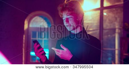 Asking. Cinematic Portrait Of Stylish Redhair Man In Neon Lighted Interior. Toned Like Cinema Effect