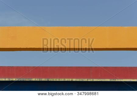 Urban Detail, A Blue And Red Wall With An Eave That Casts Shadow, A Yellow Girder And A Clear Sky, I