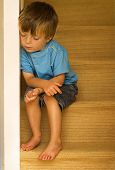 Impression of a neglected child sitting on carpeted stairway. poster